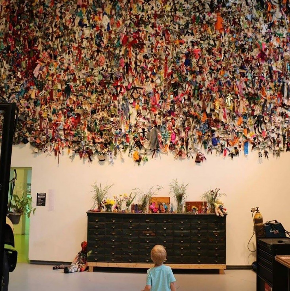 Child looking at wall with dolls attached