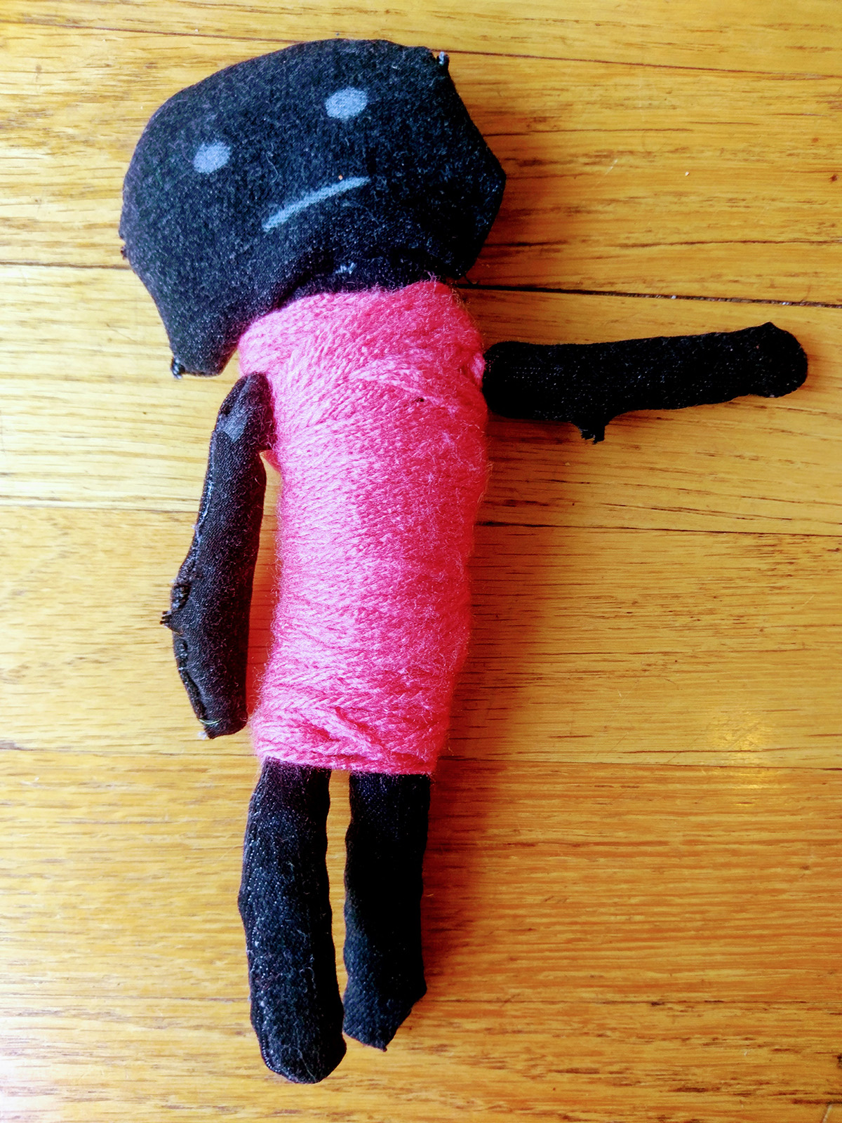 Hand-made doll with black body and pink clothing