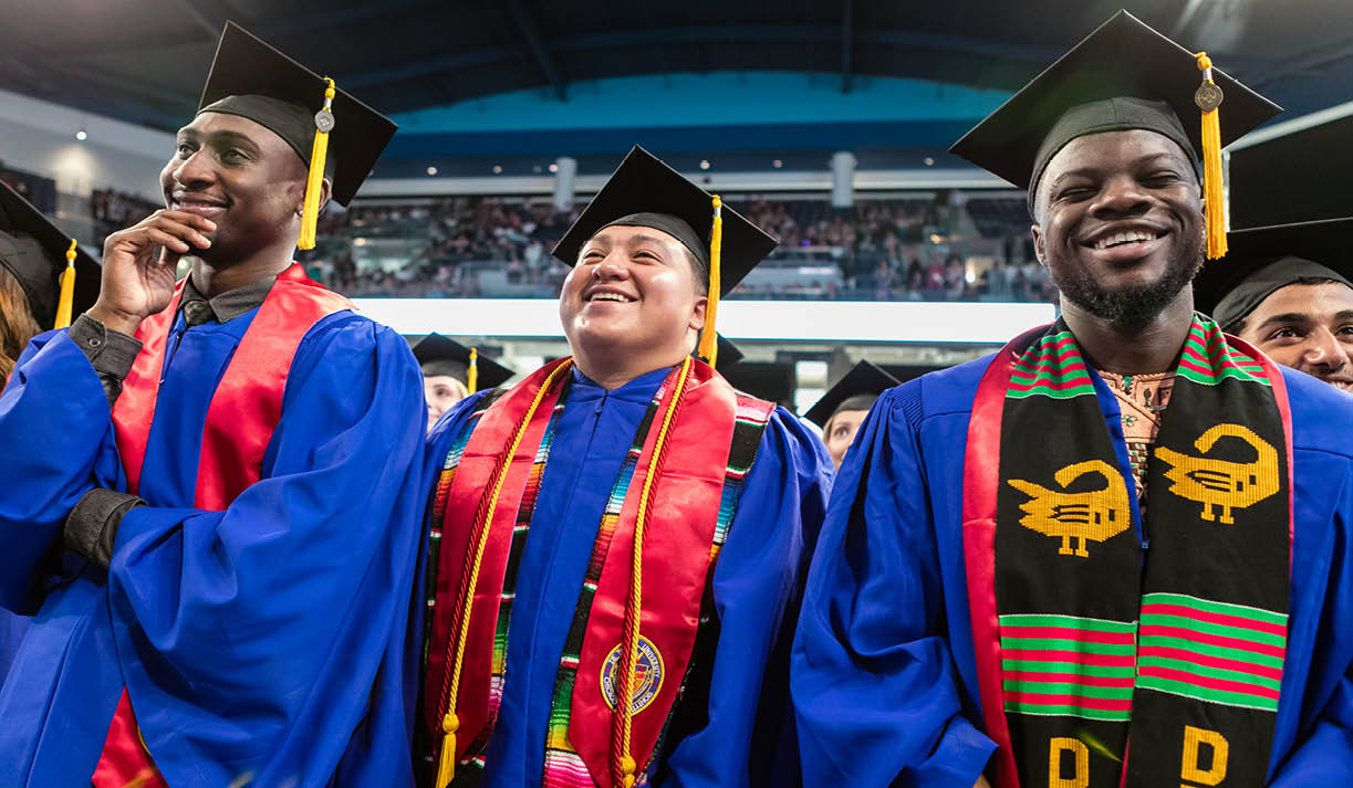 DePaul graduates smiling during their commencement ceremony celebration