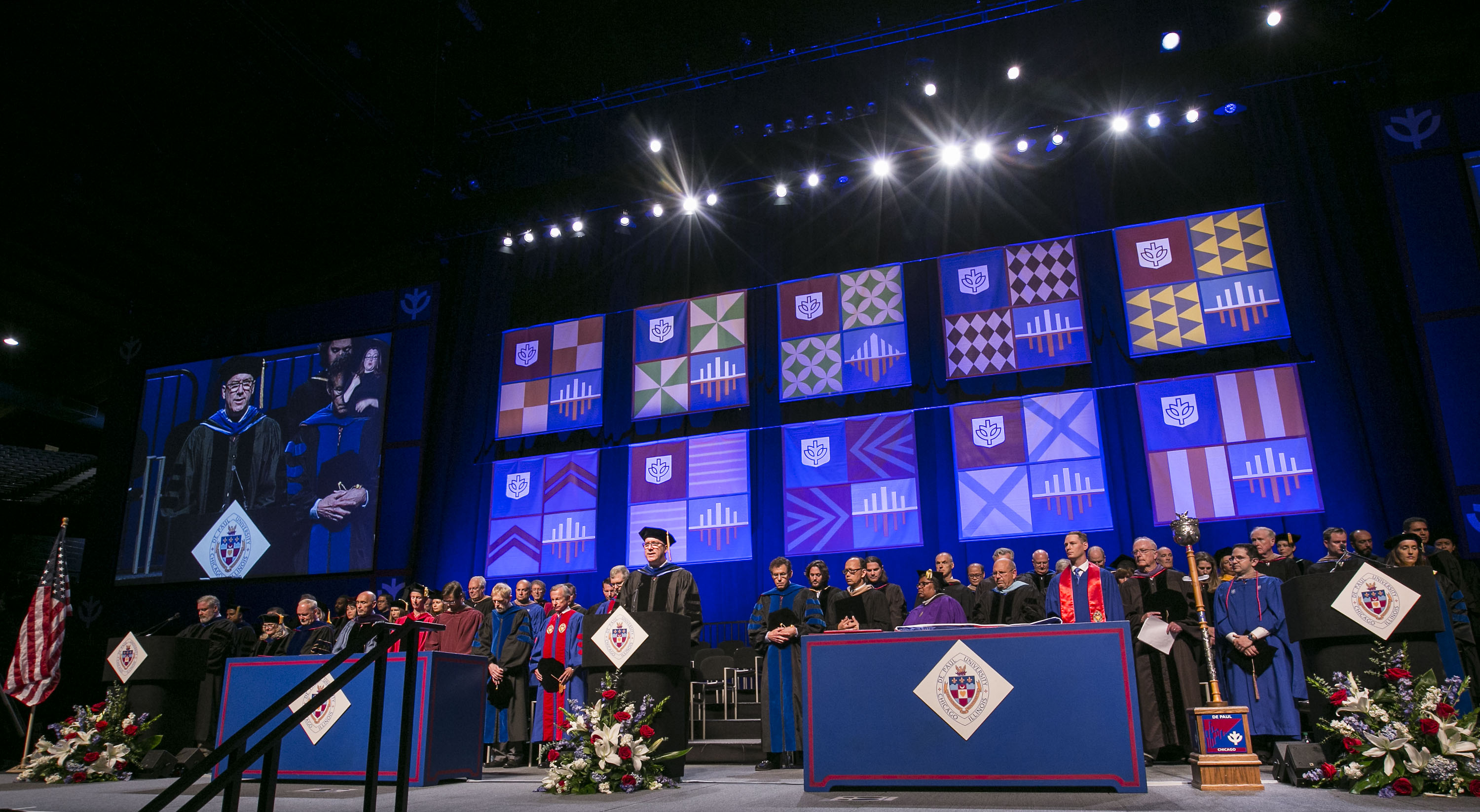Man stands at a podium on the commencement stage
