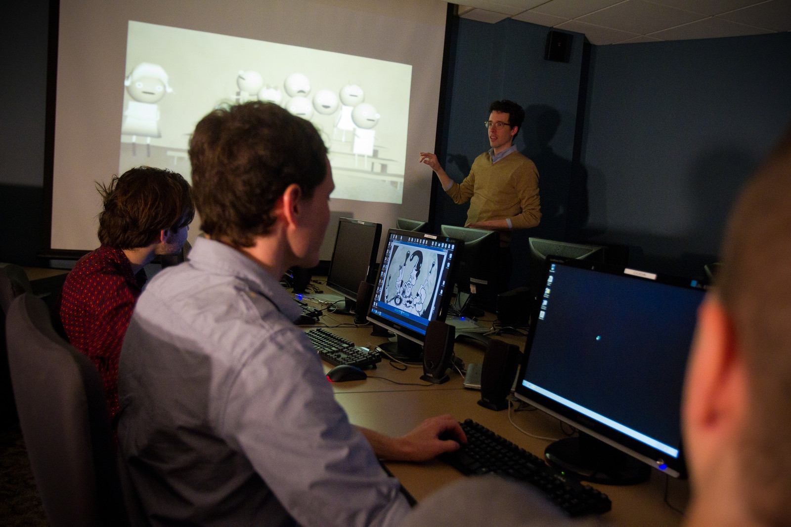 Students with computers in darkened classroom in front of projector screen