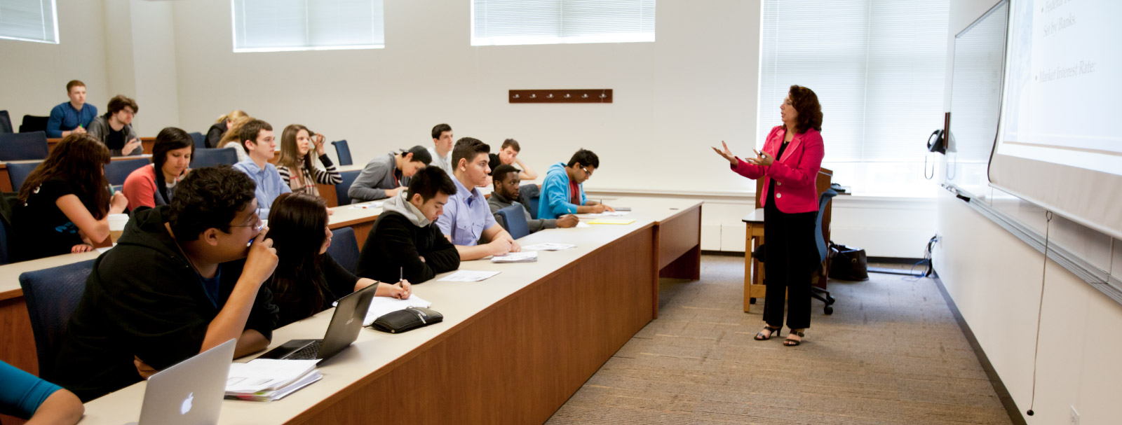 Caucasian professor lecturing in front of rows of students