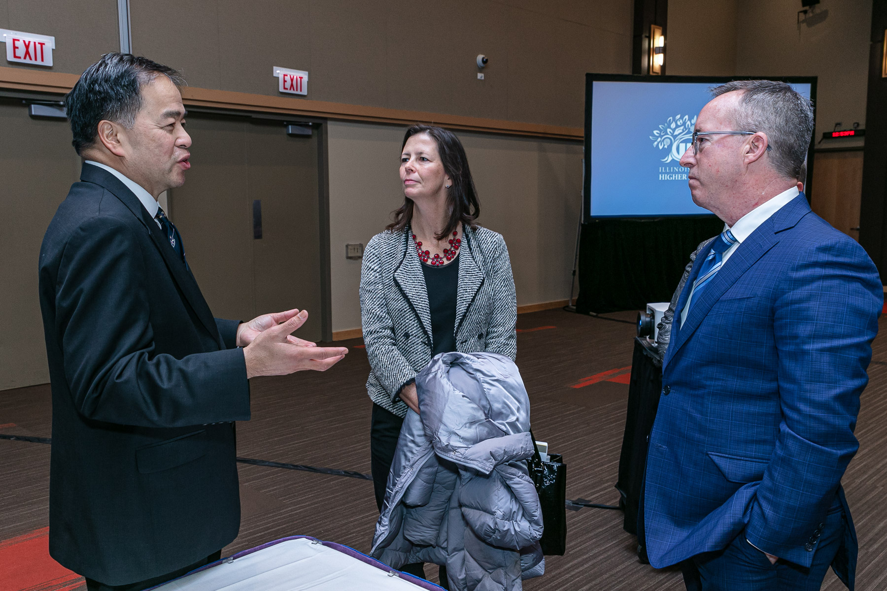 Left to right, A. Gabriel Esteban, Ph.D., president of DePaul; Illinois Rep. Kelly Burke (D); and John Atkinson, chair of Illinois Board of Higher Education; chat before the meeting begins. (DePaul University/Randall Spriggs)