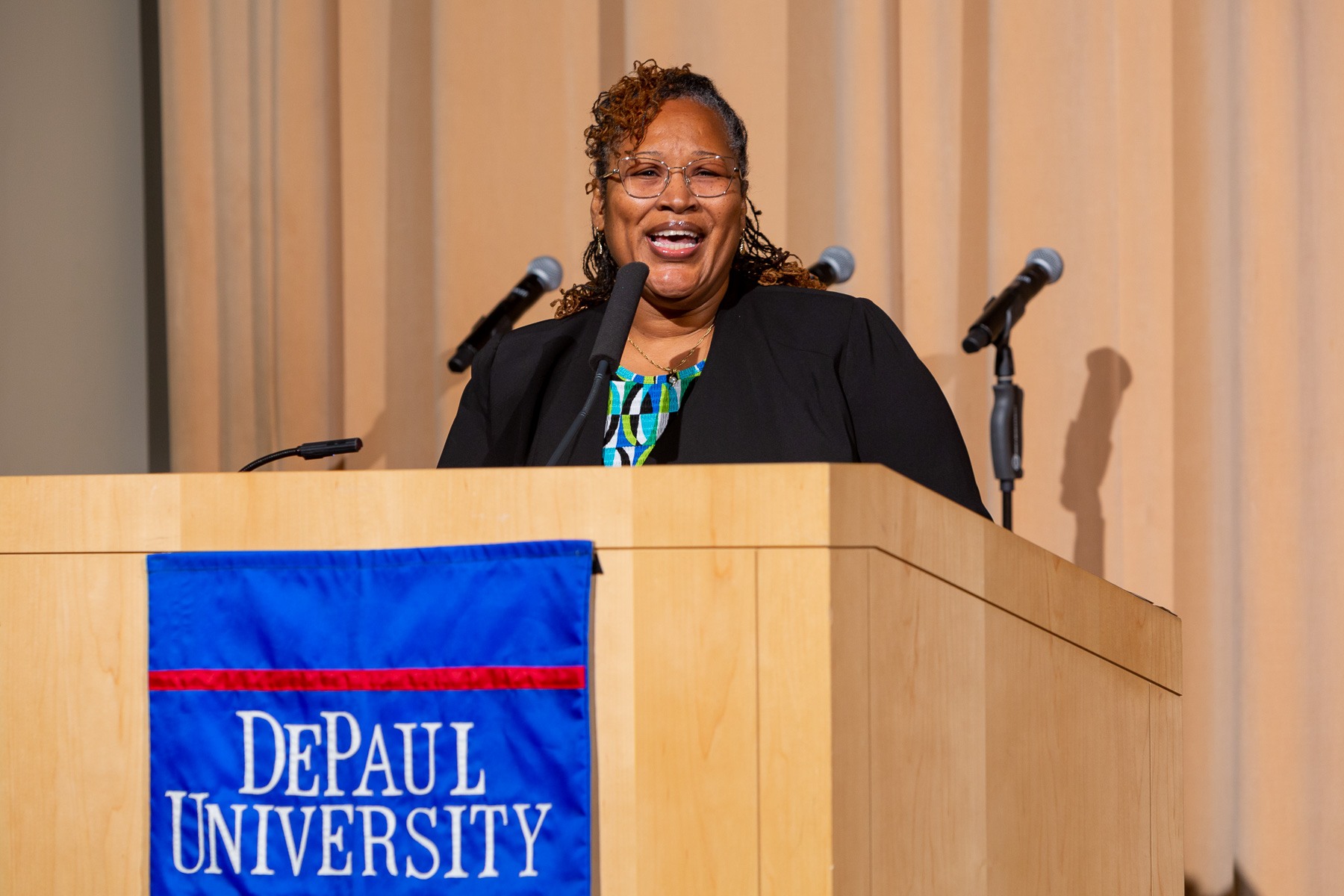 "Sandra Bowen, senior grant and contracts specialists, leads the crowd in singing, ""Lift Ev'ry Voice and Sing,"" by James Weldon Johnson. (DePaul University/Randall Spriggs)"
