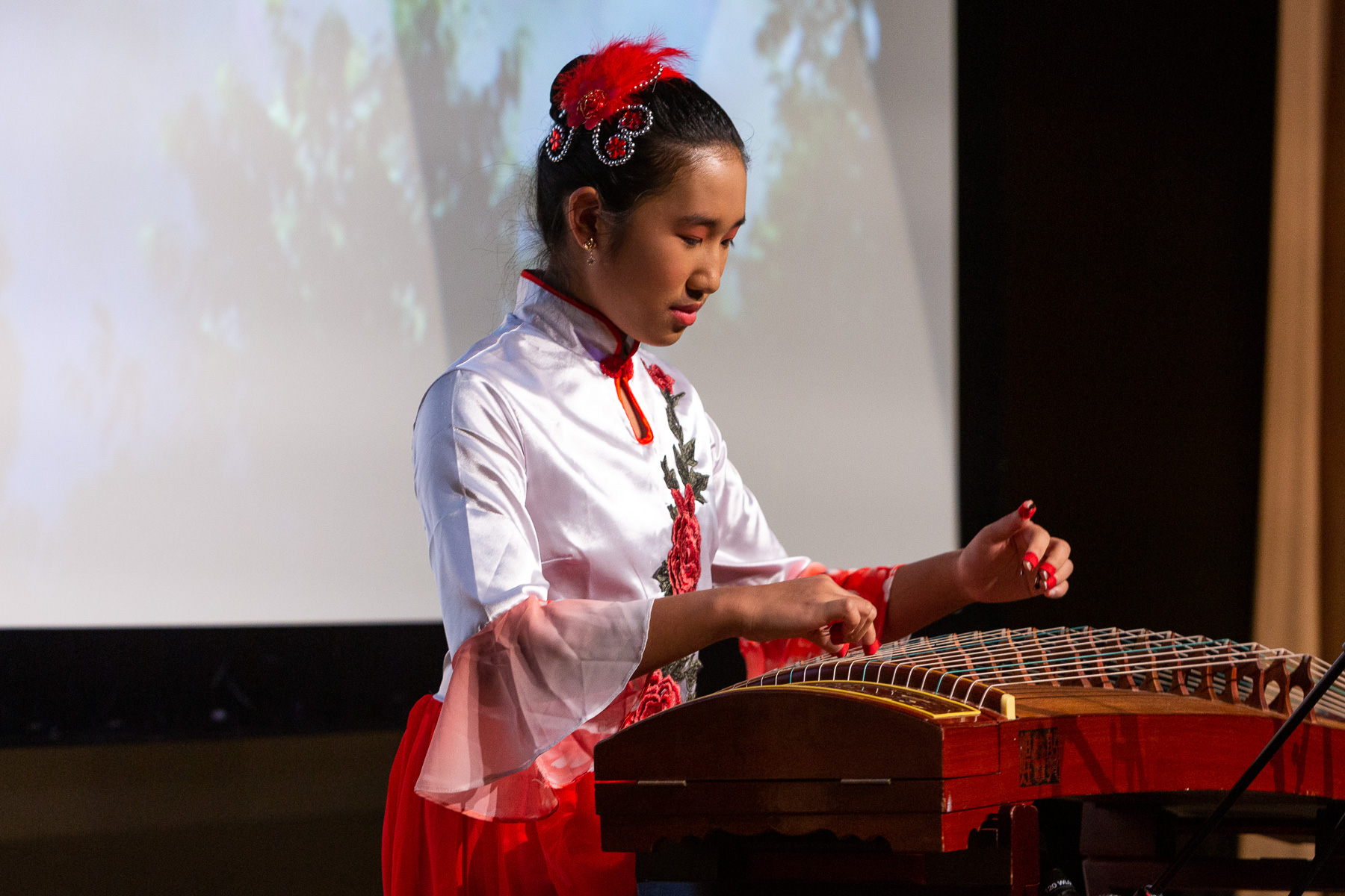"DePaul student Angela Wang performs ""Dance of the Yi People,"" using a traditional guzheng string instrument. (DePaul University/Randall Spriggs)"