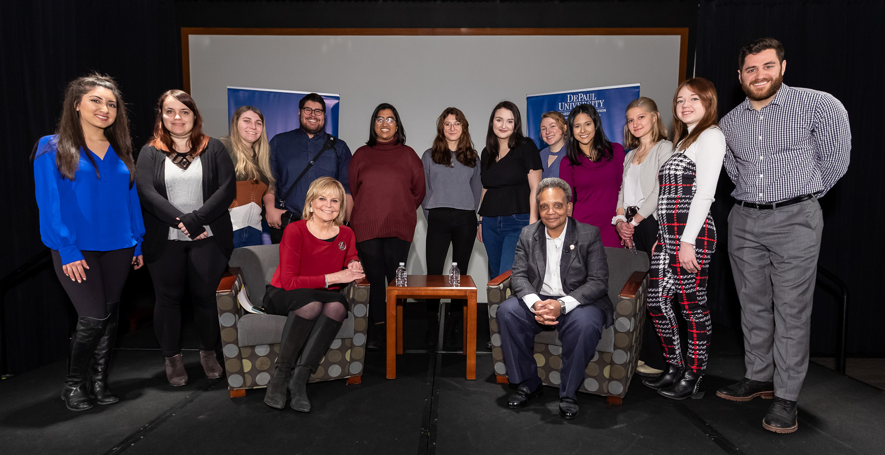 DePaul University students in Advanced Reporting pose for a photo with their instructor Carol Marin (seated left) and Chicago Mayor Lori Lightfoot. (DePaul University/Jeff Carrion)