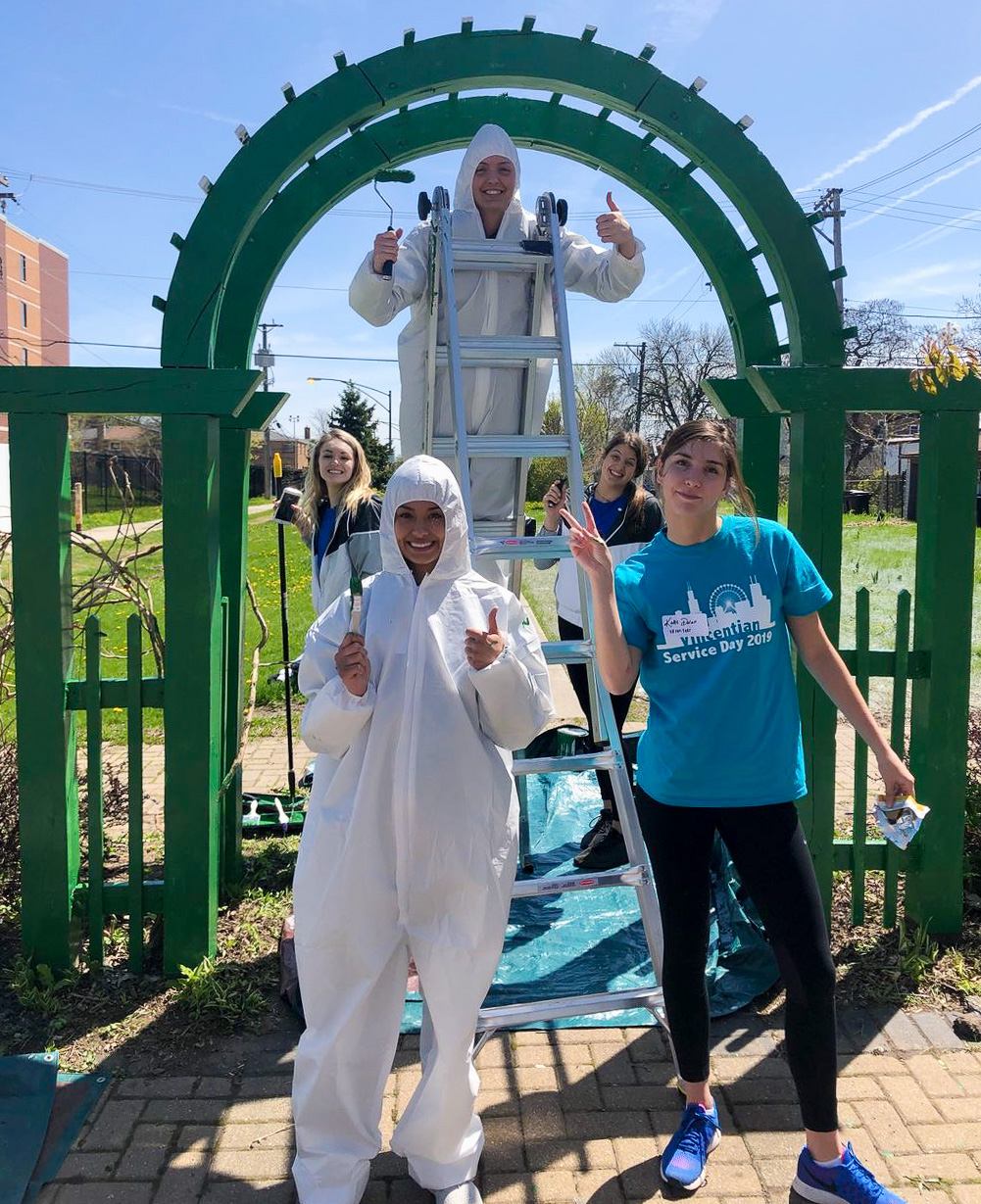 Mattie Norris, Mackenzie Savage, Brittany Maxwell, Natalie Hayward and Katie Dolan, players on the women's Volleyball team, painted exterior fencing at Neighbor Space – Chicago. (DePaul University Athletics)​