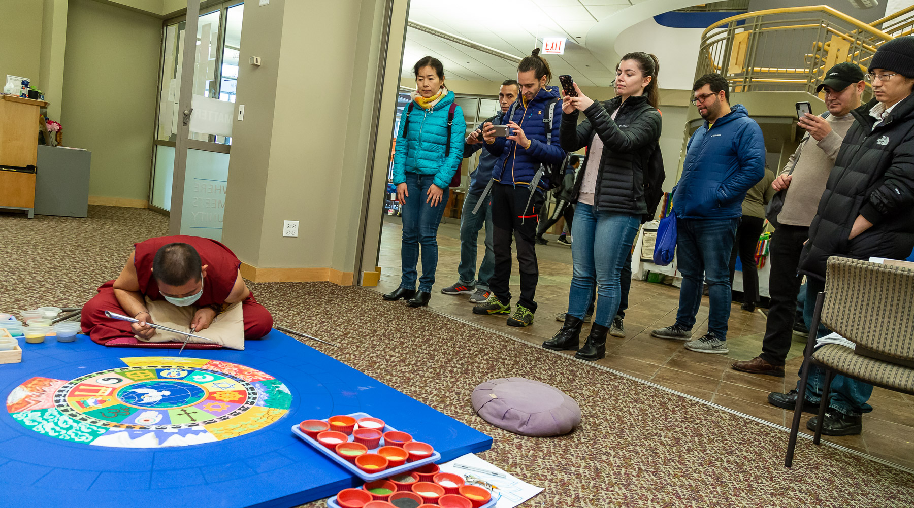 Onlookers watch a Buddhist monk create a sand mandala, Wednesday, Oct. 31, in the Lincoln Park Student Center. (DePaul University/Jeff Carrion)