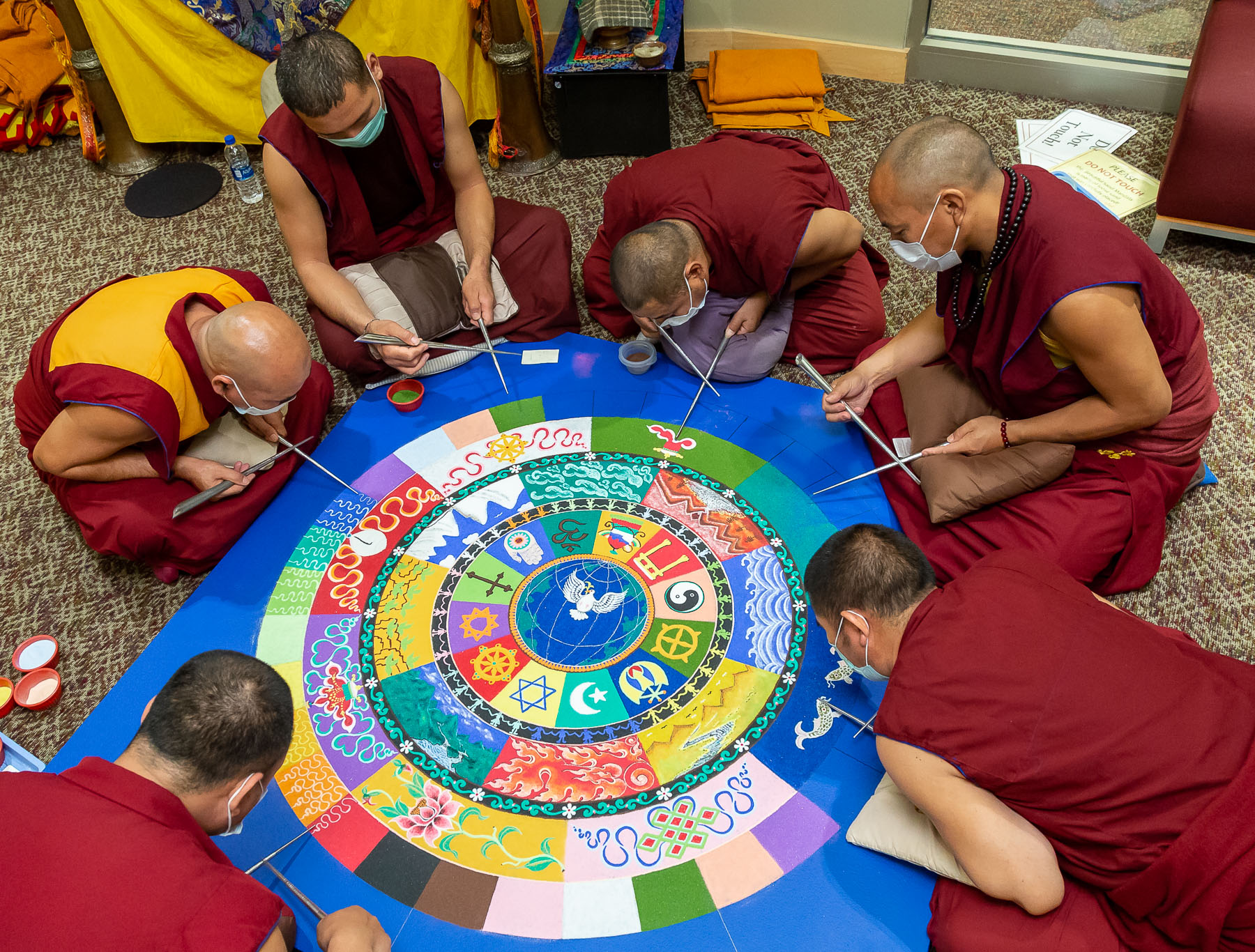 After five days of slow, meticulous progress, several monks work together to finish the mandala on Friday. (DePaul University/Jeff Carrion)