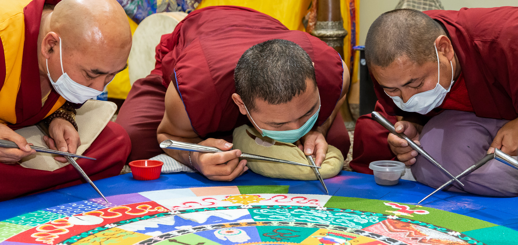 The monks rapidly rub their chak-purs together to deposit sand onto the mandala surface. They also wear masks over their mouths to avoid blowing the sand with their breath. (DePaul University/Jeff Carrion)