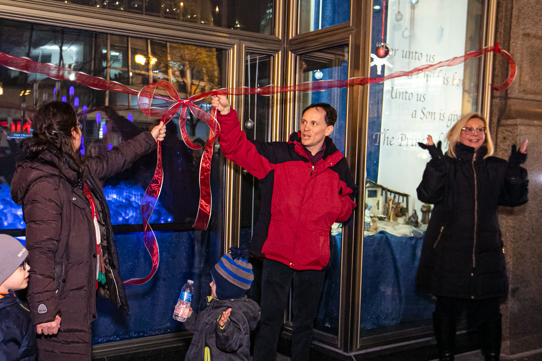 "Left to right, Meghann Artes, Devin Bell and JoAnne Zielinski unveil the ""Merry Christmas from DePaul"" film and window display. A new tradition for DePaul, the display builds on the history of magical holiday windows along State Street for more than 100 years. (DePaul University/Randall Spriggs)"