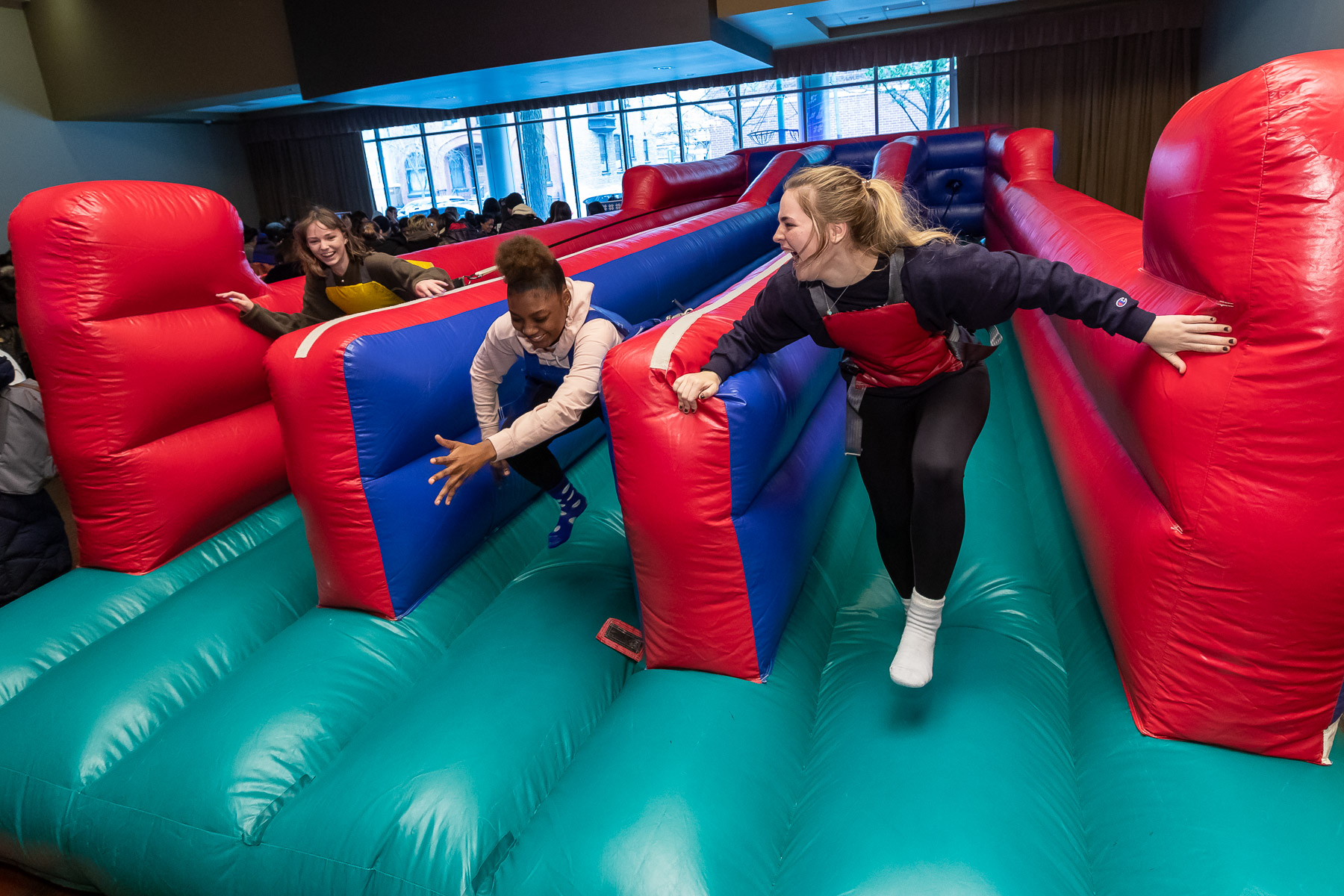 Students attempt to run against tethered harnesses in an inflatable bounce attraction in the Student Center. (DePaul University/Jeff Carrion)