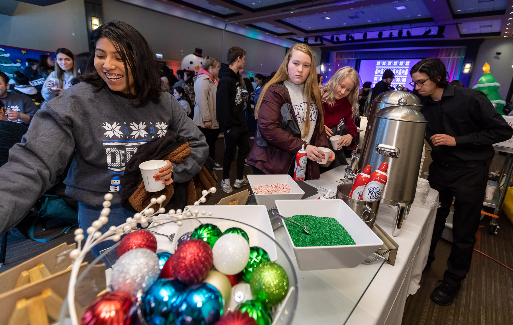 Students fill cups of hot cocoa with sweet treats. (DePaul University/Jeff Carrion)