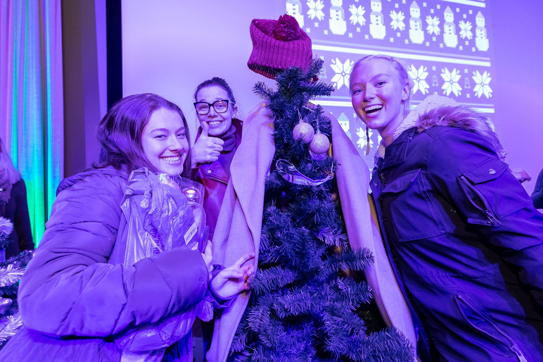 Students try their best to decorate a Christmas tree for the tree decorating contest at the Ugly Sweater Party. (DePaul University/Jeff Carrion)