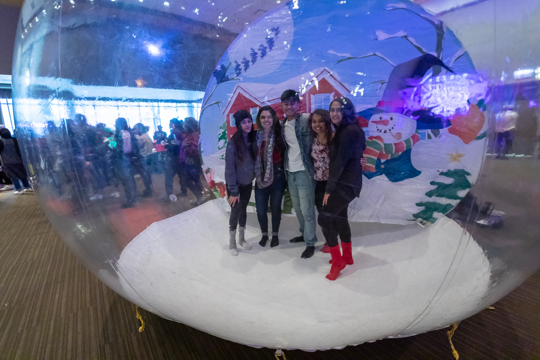 Students take pictures inside an inflatable snow globe before heading out to the Tree Lighting Ceremony. (DePaul University/Jeff Carrion)