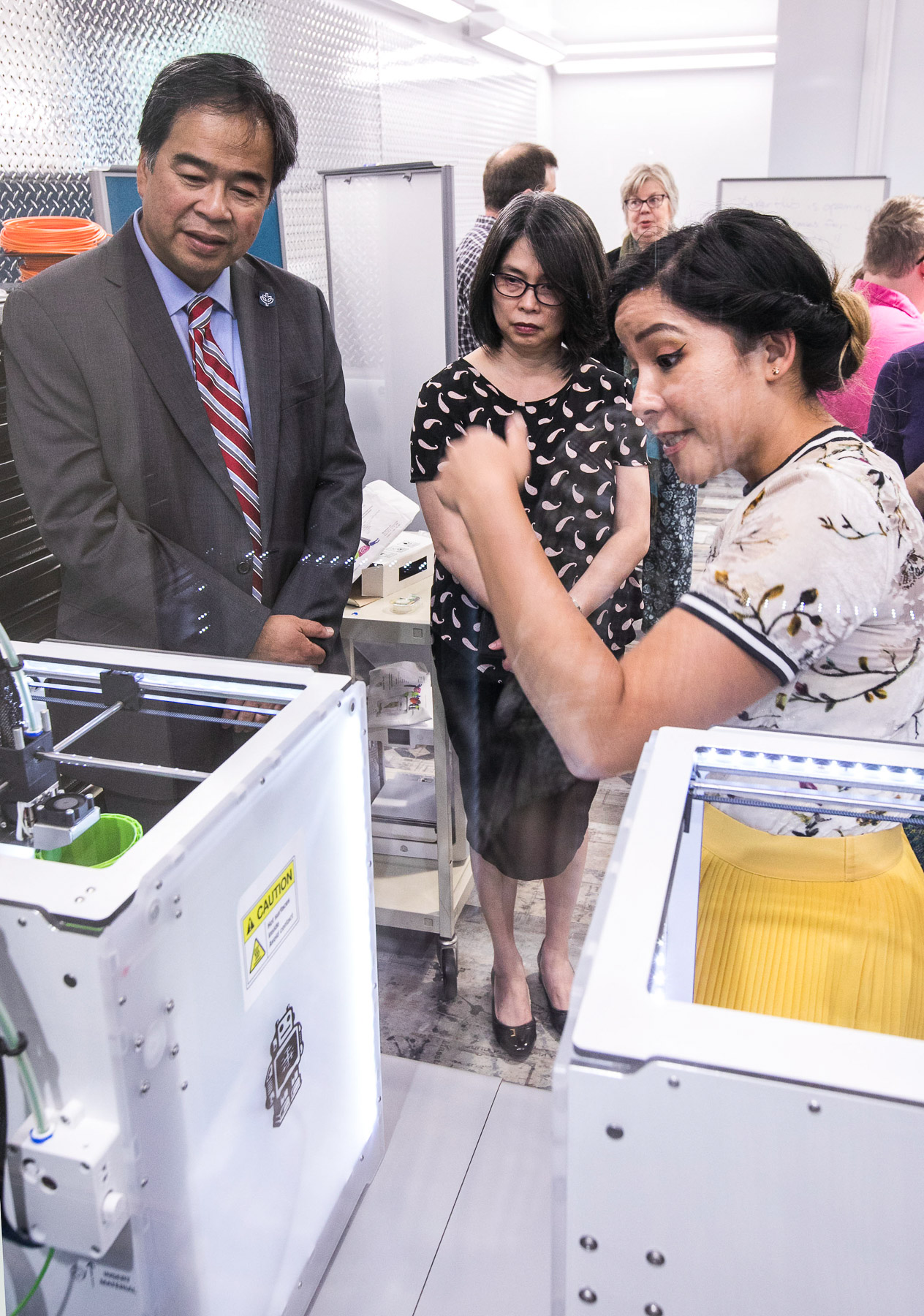 Janice Scurio, right, shows off one of the 3D printers available in the new maker space to DePaul University President A. Gabriel Esteban, Ph.D., and his wife, Josephine, as they tour the newly workspaces in the Richardson Library. (DePaul University/Jamie Moncrief)