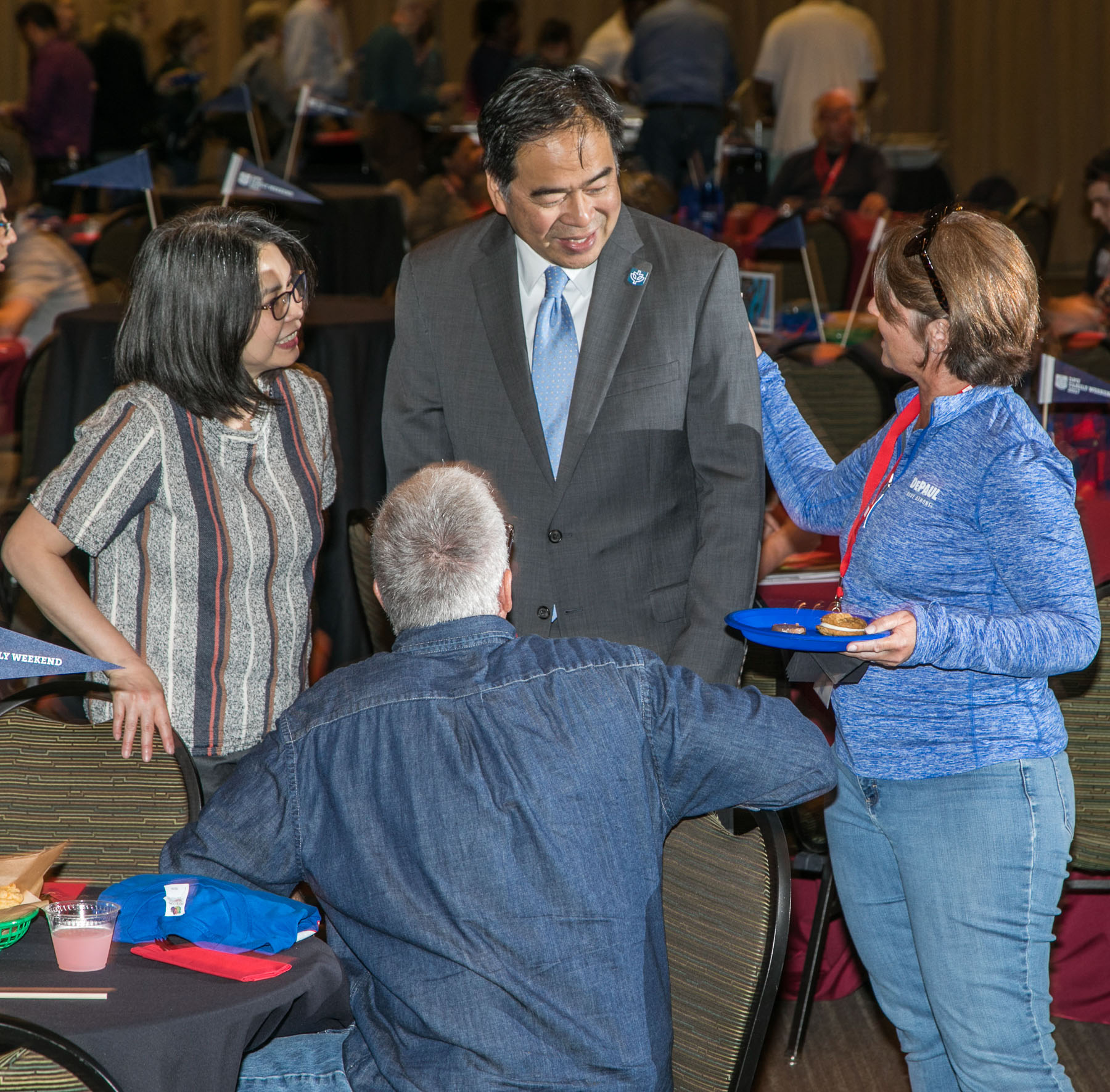 Josephine Esteban, left, and DePaul University President A. Gabriel Esteban, Ph.D., center, greet guests as students and family members gather for a buffet dinner and student performances at the Family Weekend Kickoff celebration. (DePaul University/Jamie Moncrief)