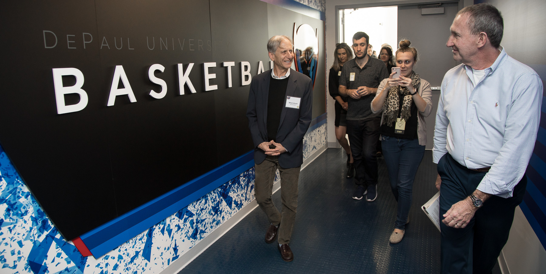 Mitchell Hirsch, principal architect for Pelli Clarke Pelli Architects, left, and Bob Janis, vice president of facility operations, lead attendees into DePaul's basketball suite. (DePaul University/Jeff Carrion)