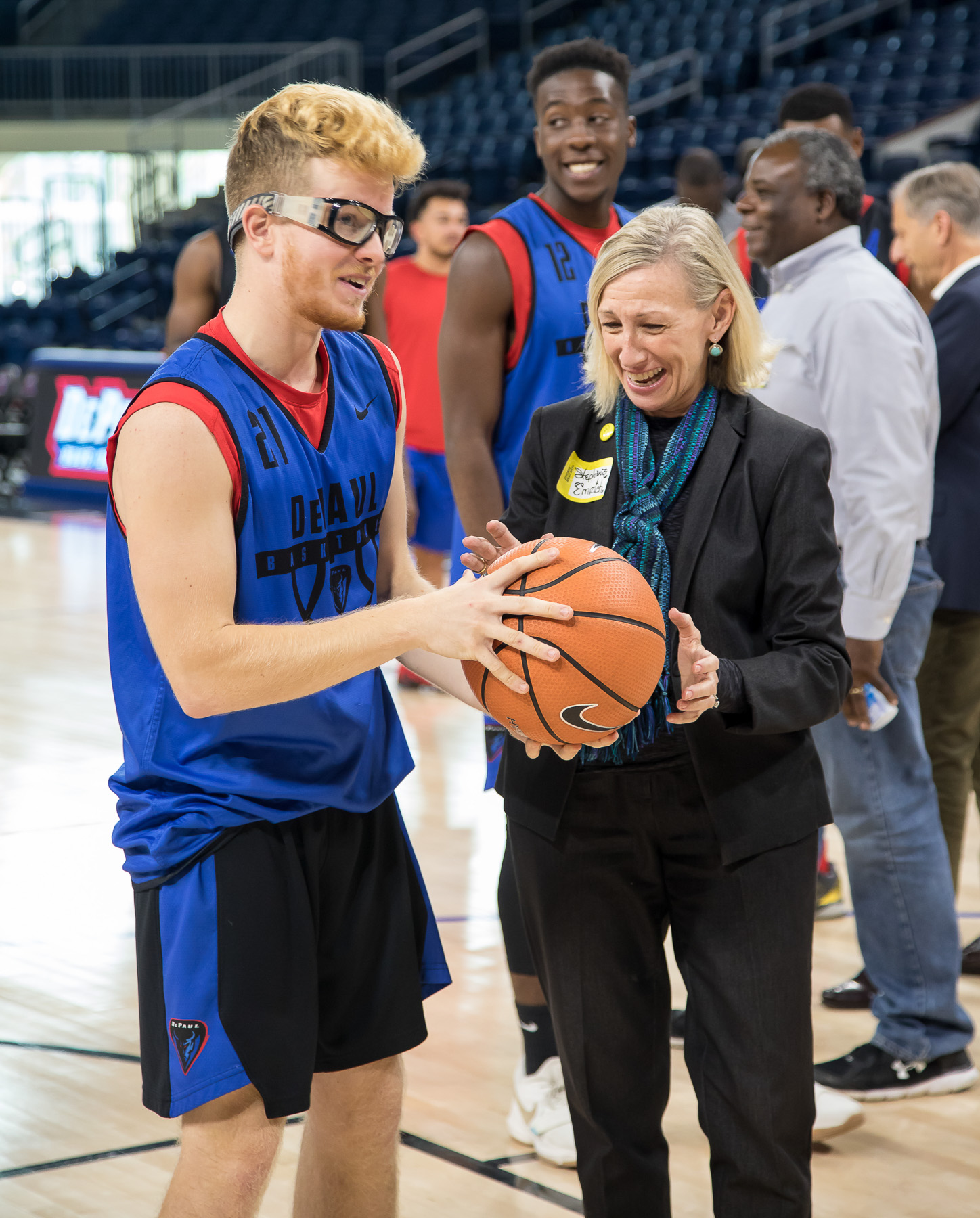 DePaul basketball player Pantelis Xidias, left, helps attendee Stephanie Emrich shoot baskets during a sneak peek of the new Wintrust Arena. (DePaul University/Jeff Carrion)