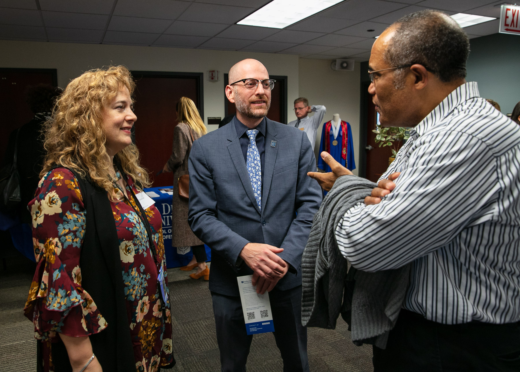 Caroline Kisel, assistant professor, left, and Don Opitz, interim dean for the School of Continuing and Professional Studies, converse with an attendee during the open house event. (DePaul University/Randall Spriggs)