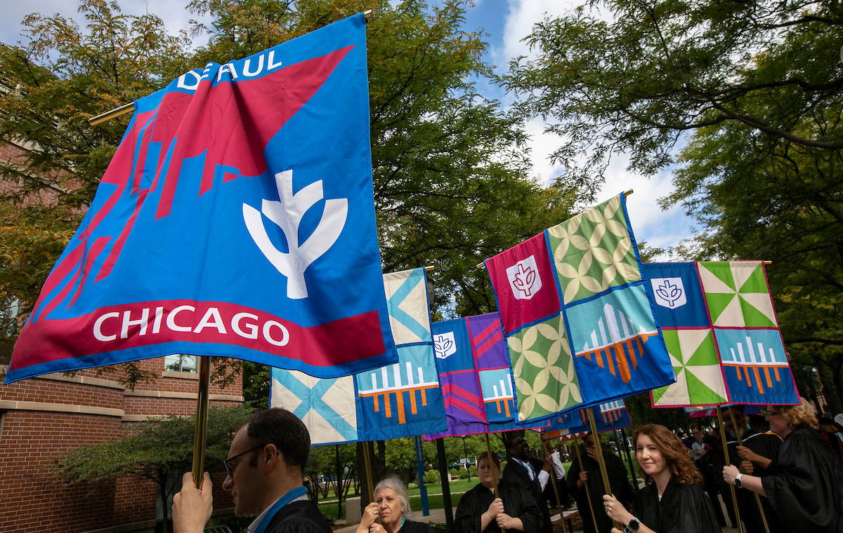 The university, college and school banners are brought to the front of the line as DePaul University faculty and staff mark the beginning of the school year during Academic Convocation at the St. Vincent de Paul Parish Church Thursday, Aug. 30, 2018, on the Lincoln Park campus. (DePaul University/Jamie Moncrief)