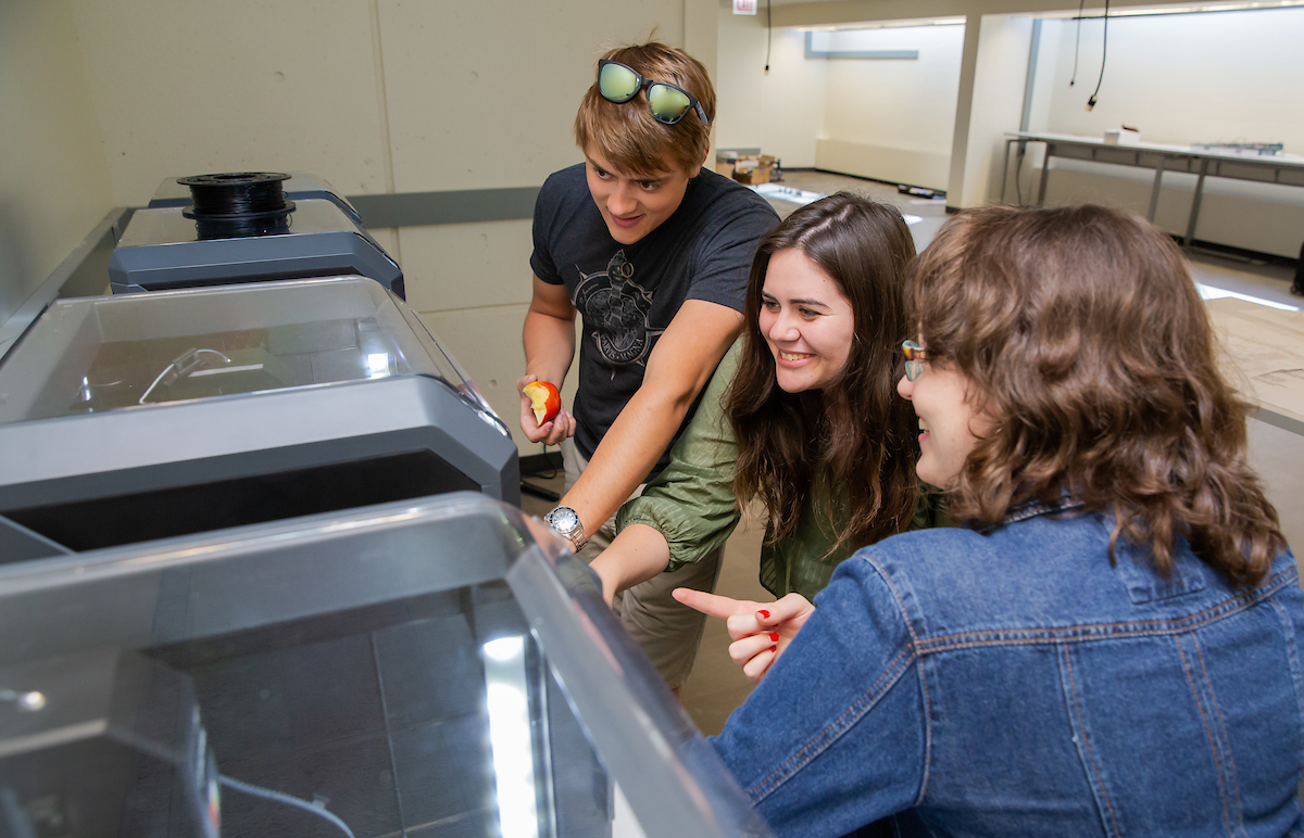 Student workers Jake Juracka, Claire Rosas and Hailey Sullivan test the functionality of a 3D printer
