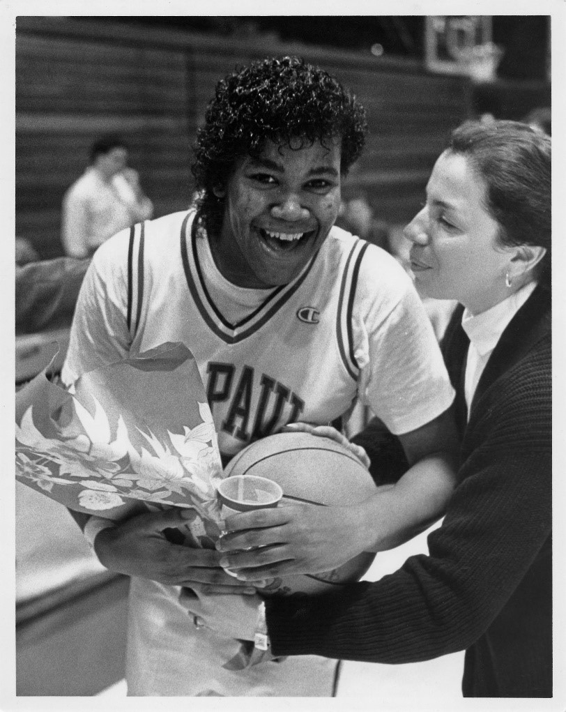 Jean Lenti Ponsetto presents Diana Vines with the game ball and flowers after breaking the scoring record on February 14, 1989.