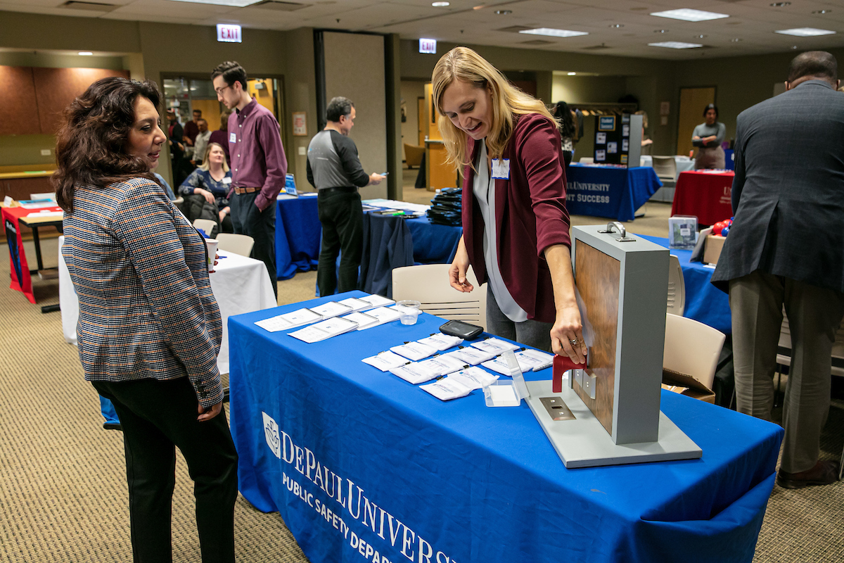 Cheryl Hover (right), associate director of emergency management in Public Safety, demonstrates the proper use of a door stopper in classrooms during the Adjunct Faculty Resource Fair in fall 2019. (DePaul University/Randall Spriggs)