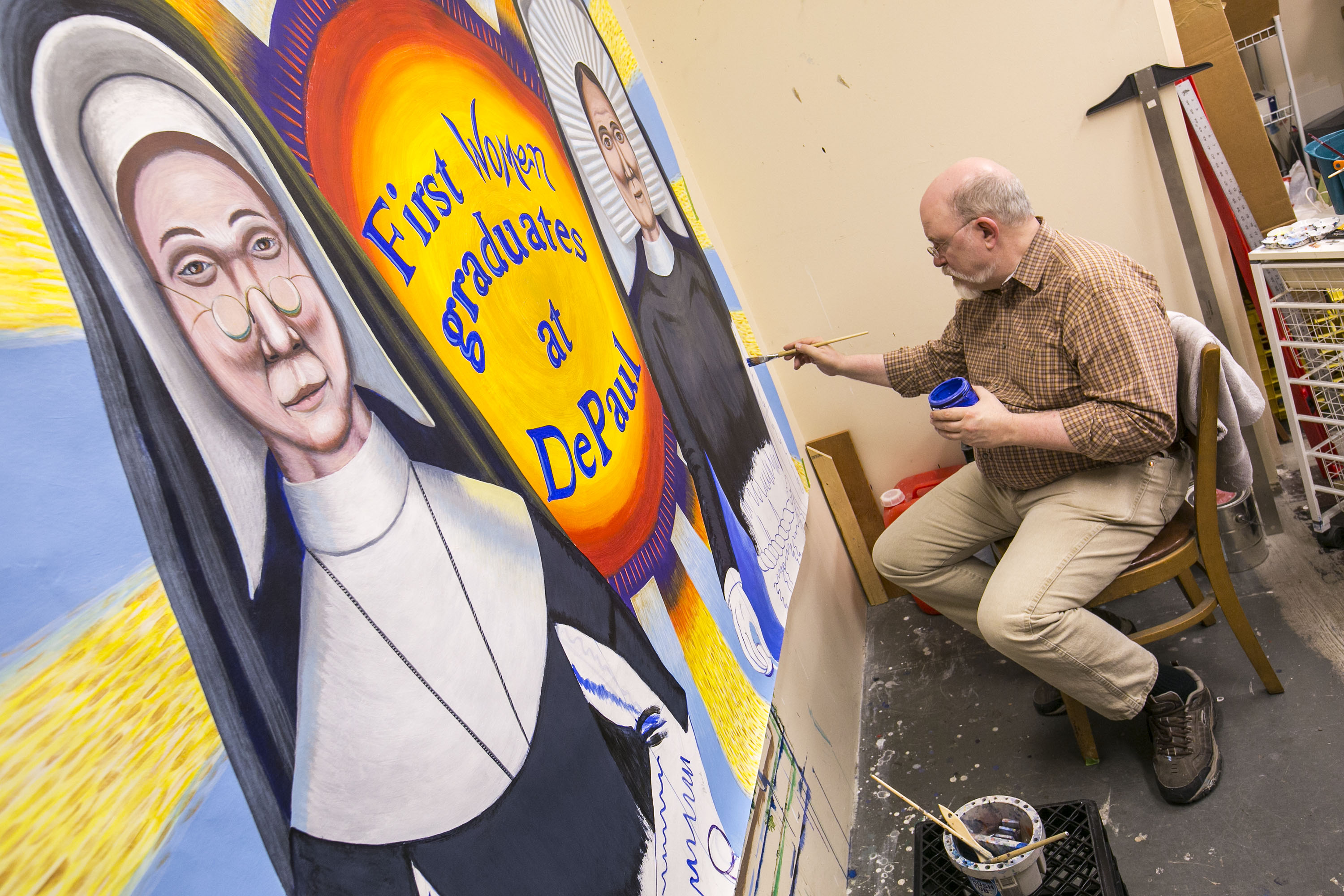 Brother Mark Elder, C.M., adds the finishing touches to the mural depicting the first women graduates of DePaul University.  (DePaul University/Jamie Moncrief)
