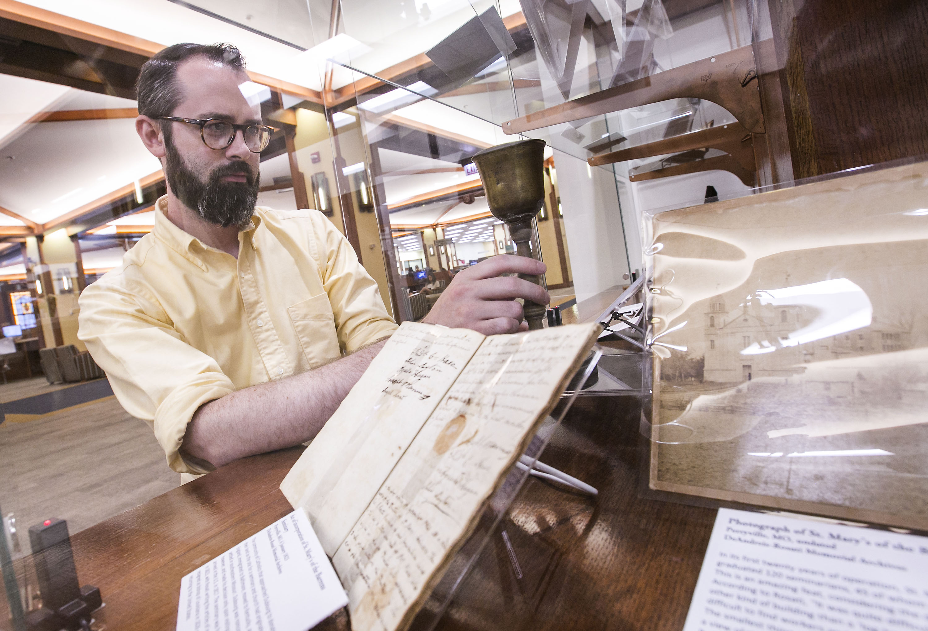 Andrew Rea, DePaul's Vincentian Librarian, places a small wooden chalice into a display case as he prepares for an exhibit of Vincentian artifacts at the John T. Richardson Library. (DePaul University/Jamie Moncrief)