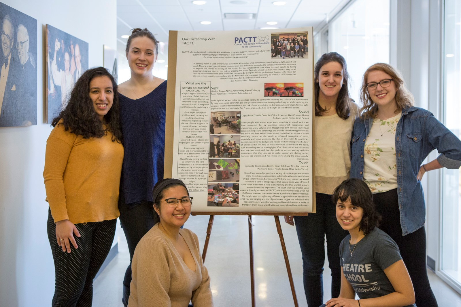 A group of students displaying their poster on community-based service learning