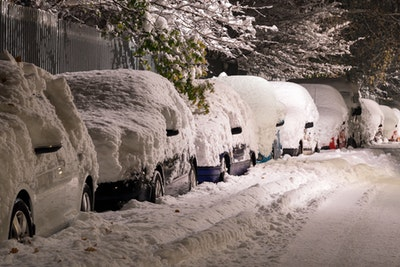 Cars blanketed in a thick covering of snow.